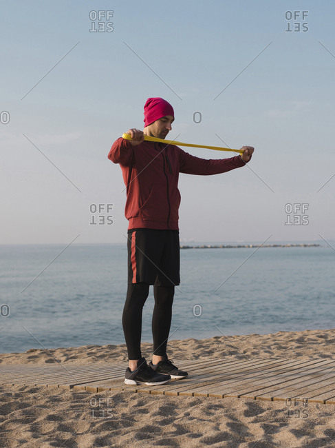 Full length of man using resistance band while exercising at beach against sky