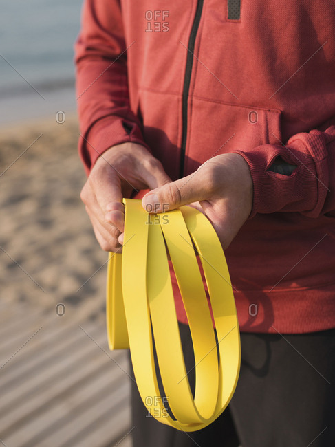 Midsection of man holding resistance band while standing at beach