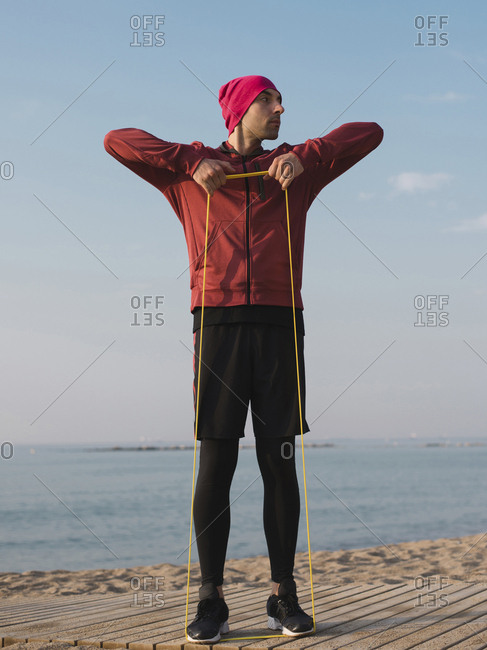 Full length of man pulling resistance band while exercising at beach against sky