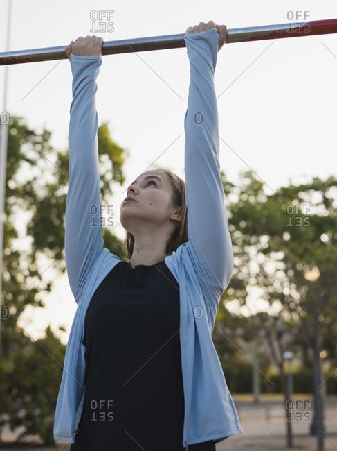 Confident woman holding gymnastics bar while exercising in park