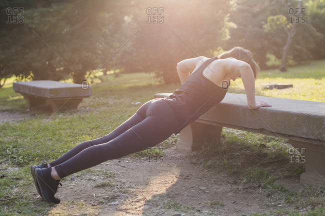 Full length of woman practicing push-ups on bench in park