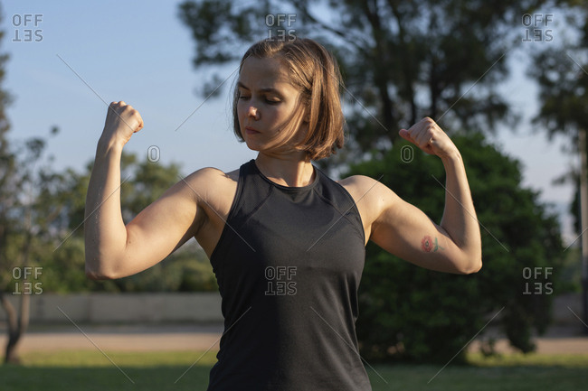Confident muscular woman flexing muscles while standing in park