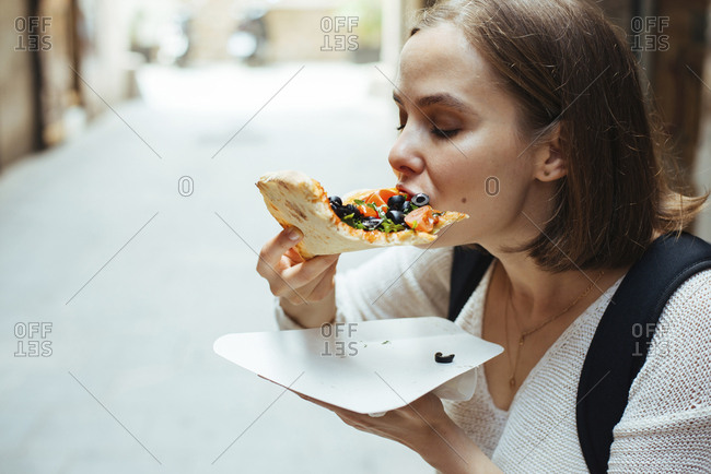 Woman eating pizza in city