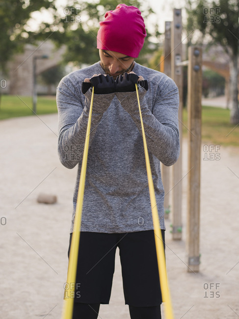 Male athlete pulling resistance band while standing at park