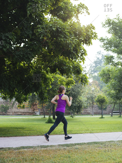 Rear view of female athlete running on footpath at park