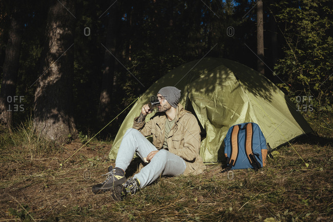 Full length of hiker drinking coffee while sitting against tent in forest