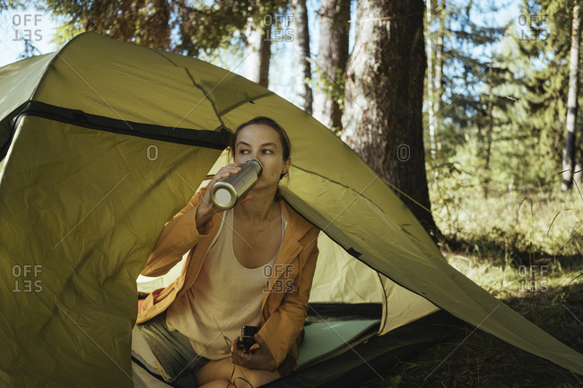 Female hiker drinking drink while sitting in tent at forest
