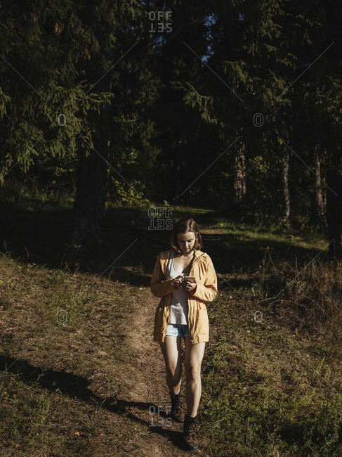Full length of female hiker using mobile phone while walking in forest during sunny day