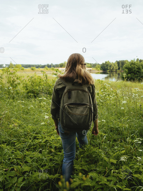Rear view of woman with backpack walking amidst plants on field in forest