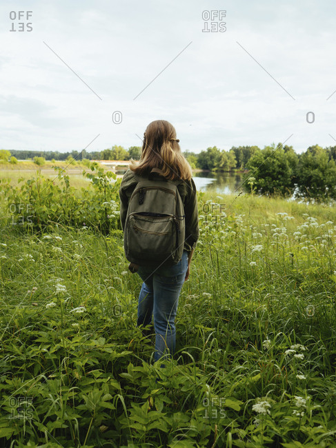 Rear view of woman carrying backpack while walking amidst plants on field in forest