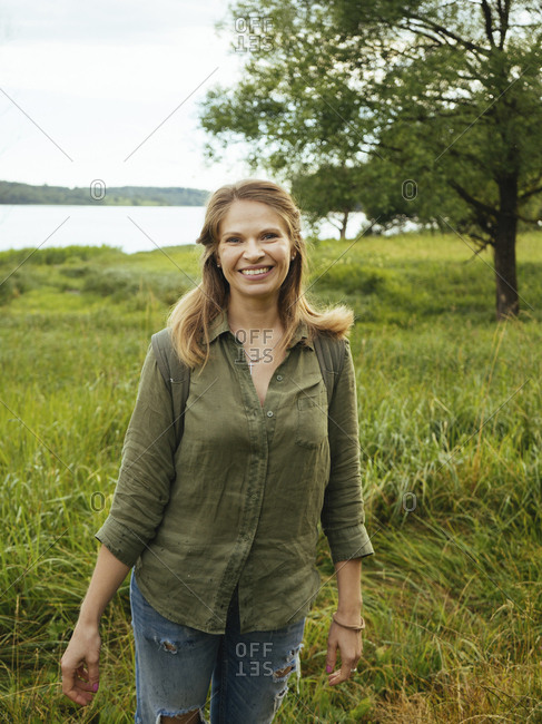 Portrait of smiling woman standing on grassy field against lake in forest