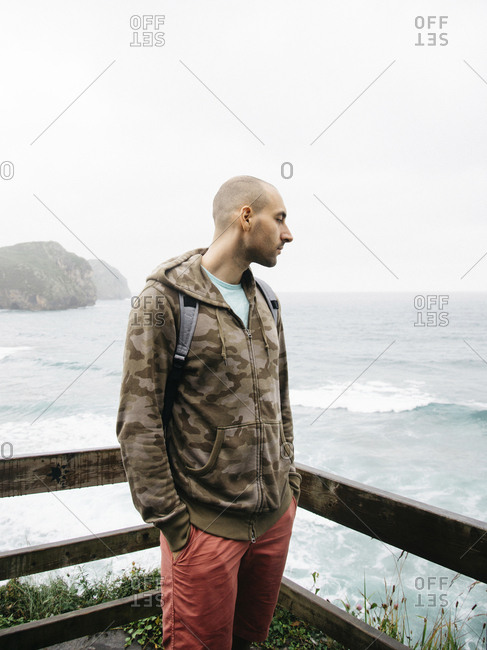 Man looking at sea while standing at observation point against clear sky