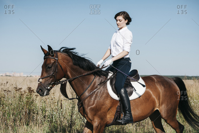 Side view of female equestrian riding horse on grassy field against clear blue sky during sunny day