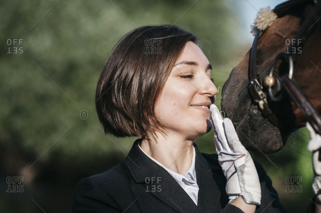 Close-up of smiling female rider stroking horse against trees during sunny day