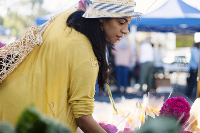 Mature woman buying flowers at farmer's market
