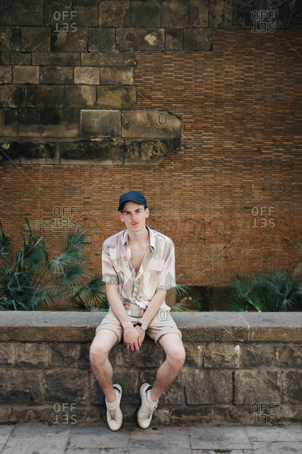 Portrait of confident man wearing cap while sitting on retaining wall