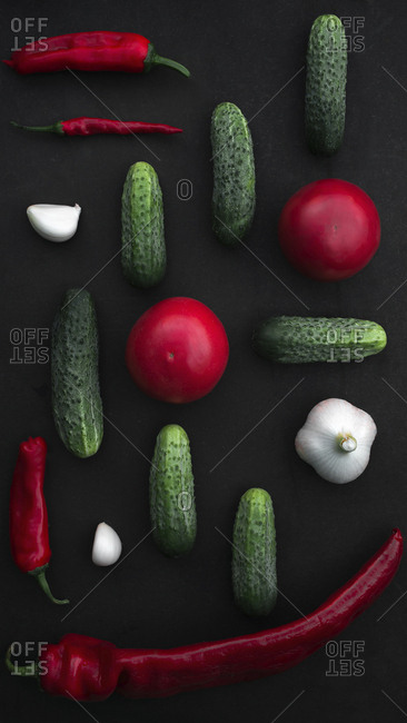 Overhead view of various vegetables and spices arranged on black background