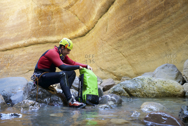 Side view of male hiker with backpack sitting on rocks in river