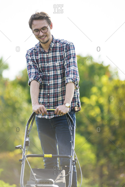 Happy man mowing at yard against clear sky during sunny day
