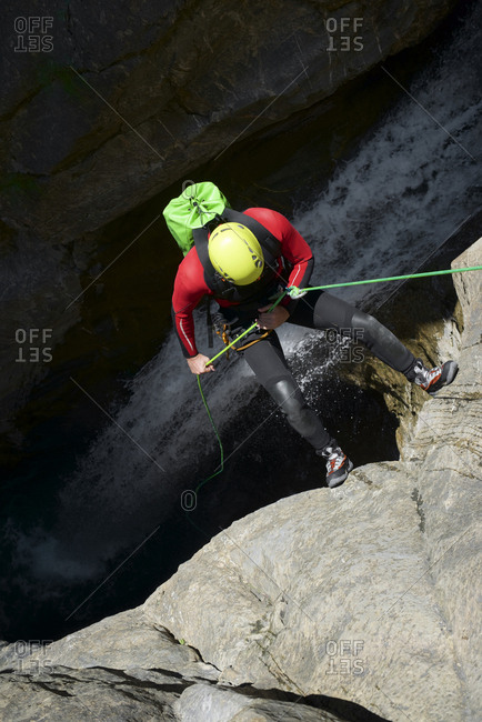 High angle view of male hiker rappelling on Pyrenees over waterfall