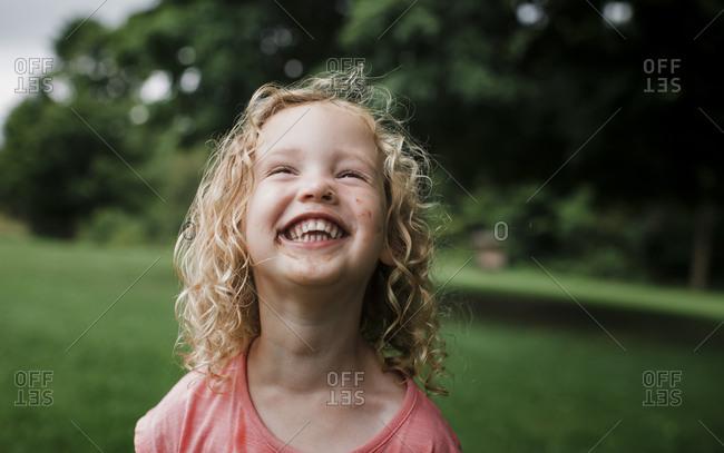 Cute cheerful girl looking away at park
