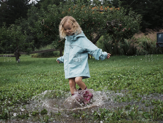 Playful girl splashing water in puddle at apple orchard