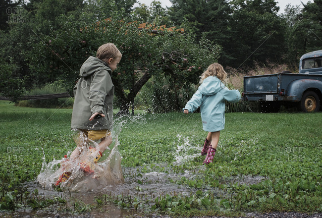 Playful siblings splashing water in puddle at apple orchard