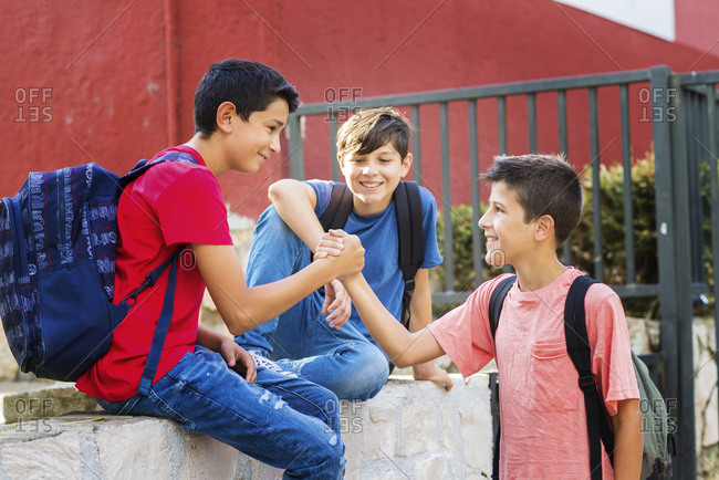 Smiling boy looking at friends giving handshake while sitting on retaining wall against school building