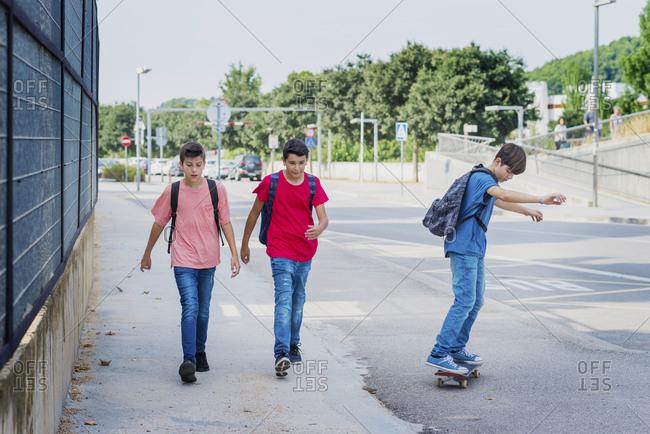 Friends walking with boy skateboarding on street