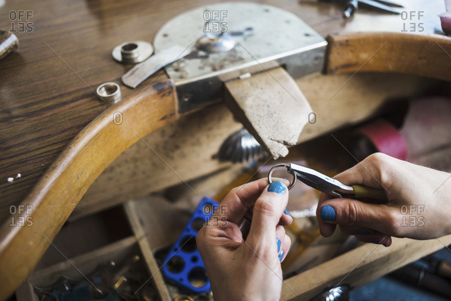 Cropped hands of female jeweler making ring with pliers at workbench in workshop