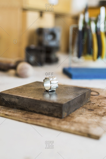 Close-up of silver ring on metal in workshop