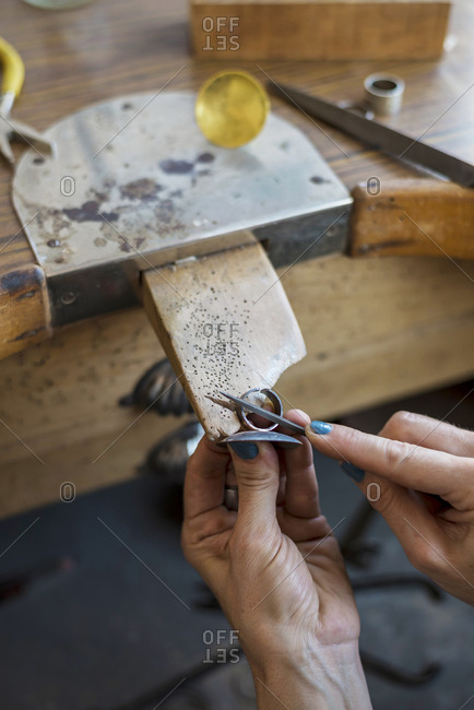Cropped hands of female jeweler filing ring with rasp in workshop