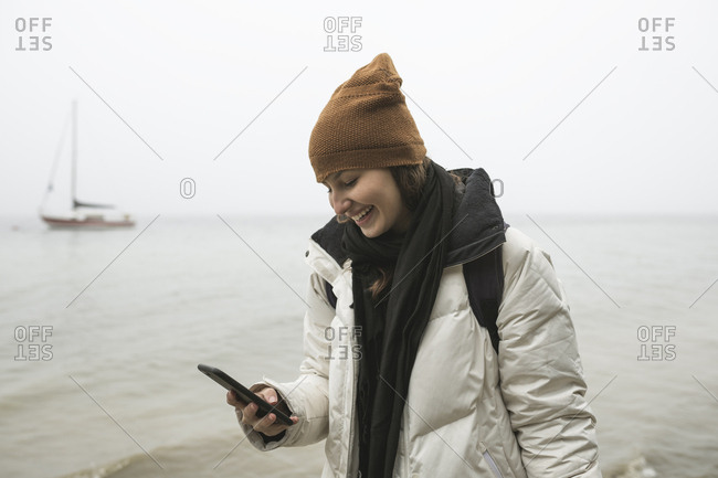 Smiling young woman using smart phone at beach during winter
