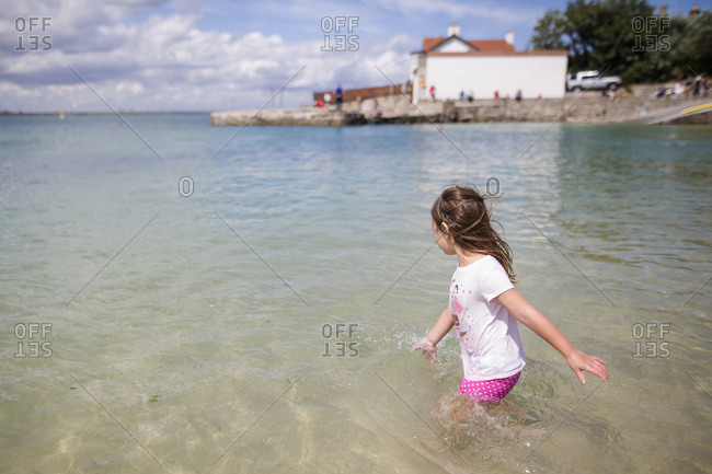 Side view of carefree girl wading in sea