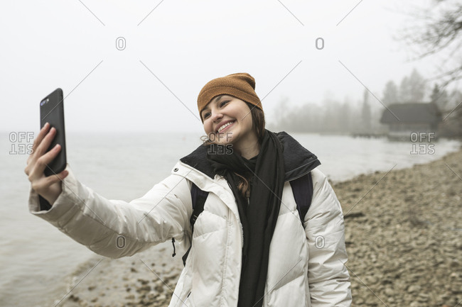 Smiling young woman taking selfie with smart phone at beach during winter