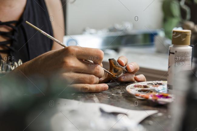 Midsection of female sculptor coloring sculpture at desk in workshop