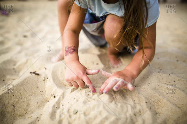 Low section of girl playing with sand at beach