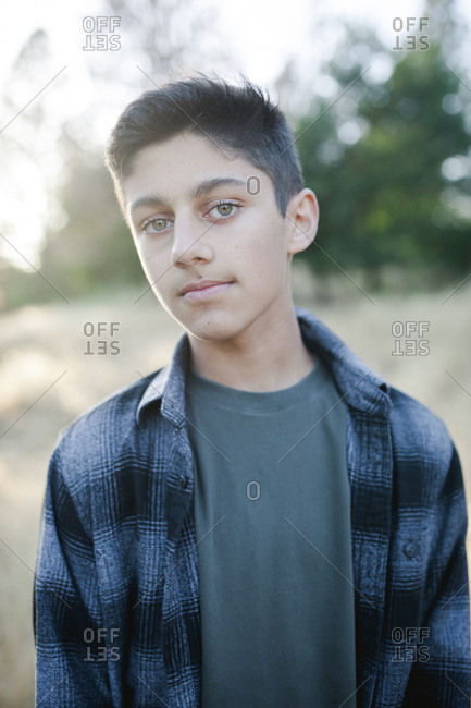 Portrait of confident teenage boy wearing jacket standing at park