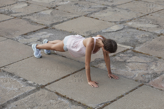 High angle view of woman doing push-ups on street in city