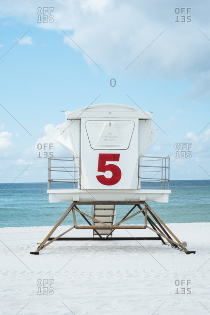 Number on lifeguard hut at beach against sea and sky