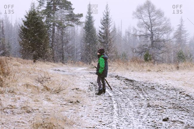 Boy standing in snowstorm