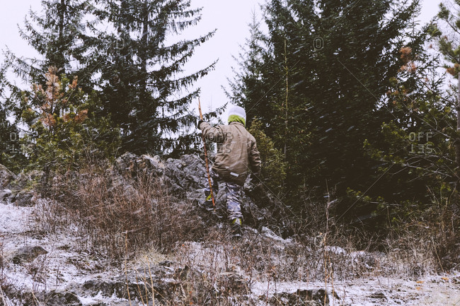 Boy climbing on rock pile in a forest in the winter