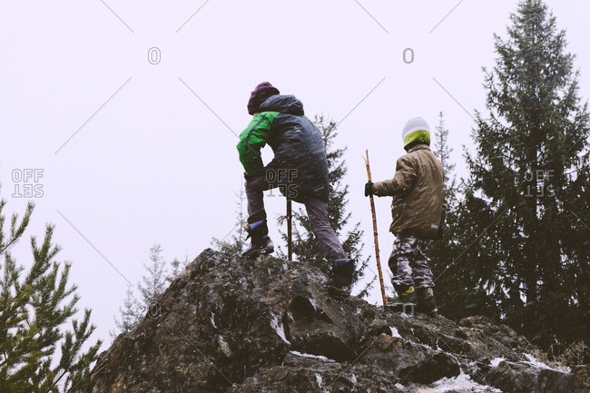 Two boys climbing on rock pile in a forest in the winter