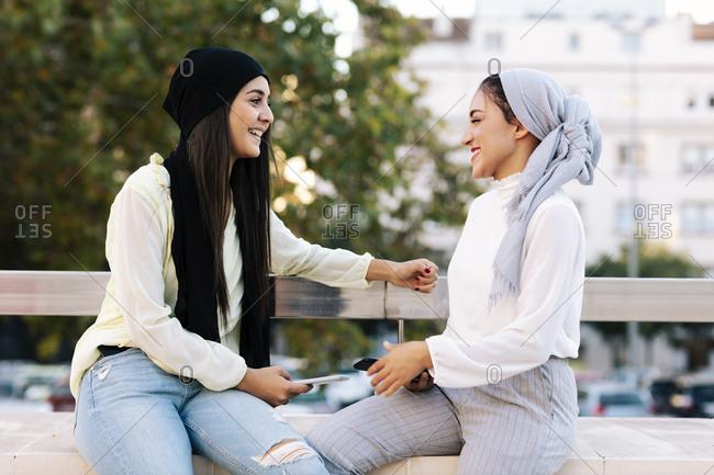 Two happy Muslim women talking on the street
