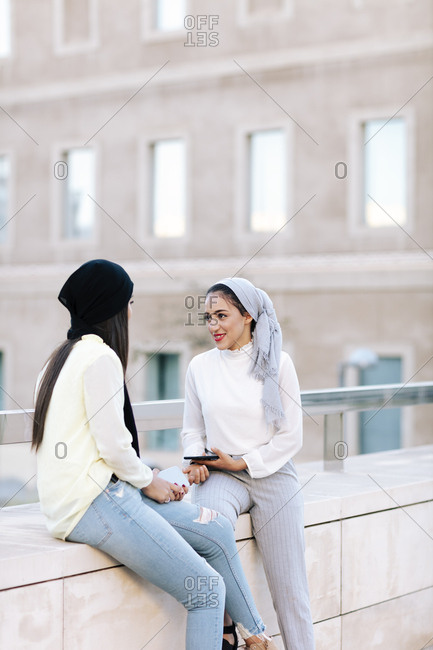 Two young happy Muslim women talking on the street