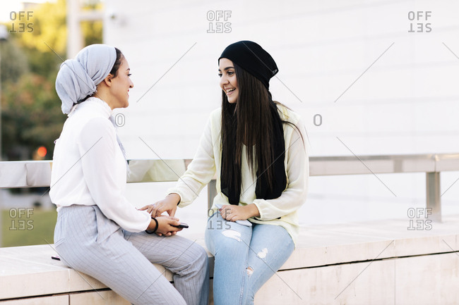 Young couple of Muslim girls talking on the street