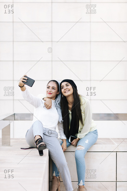 Two young Muslim women taking selfies