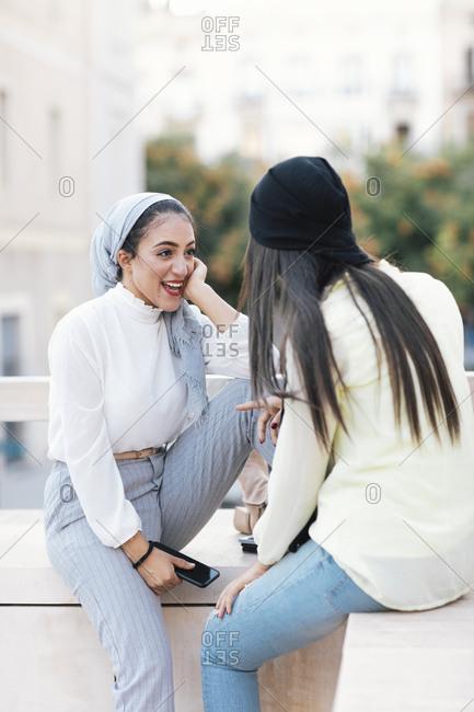 Two Muslim women talking on city street