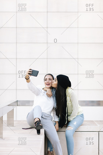 Two young Muslim women kissing and taking selfies
