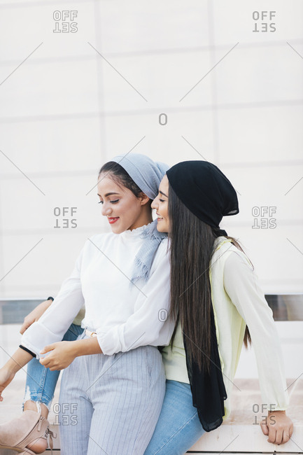 Two young Muslim women cuddling on city street